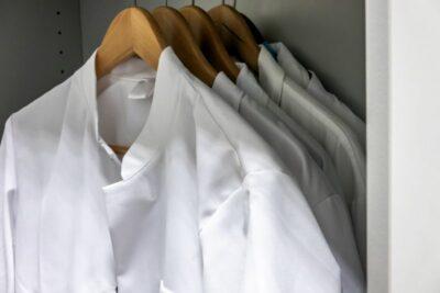 Arbeitskleidung auf Bügeln in einem Schrank