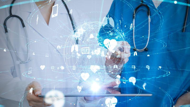 Arzt und Ärztin mit Tablet vor einer vernetzten Wektkugel