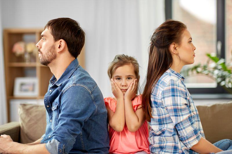 Kind sitzt zwischen den Eltern, die sich den Rücken zukehren