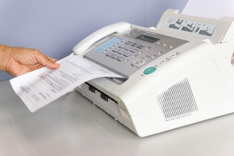 Person holt Fax aus Faxgerät