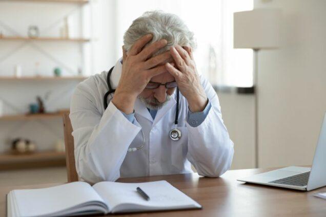 Verzweifelter Arzt am Schreibtsich