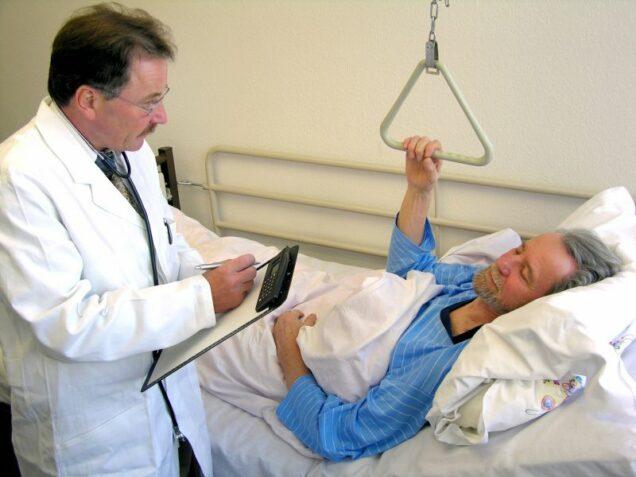 Arzt sitzt bei einer älteren Frau am Krankenbett und übermittelt eine Diagnose