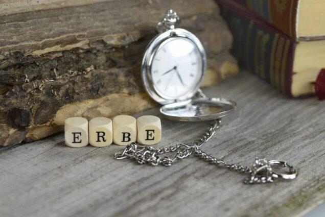 """Das Wort """"Erbe"""" auf Würfeln und eine Taschenuhr"""