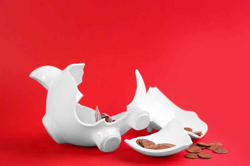 Broken piggy bank with money on red background