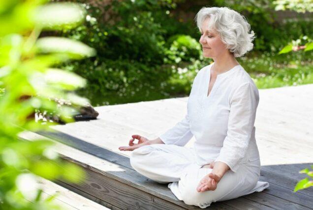 Seniorin macht Yoga im sommerlichen Garten