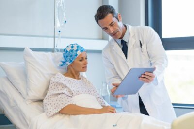 Doctor telling to patient woman the results of her medical tests. Doctor showing medical records to cancer patient in hospital ward. Senior doctor explaint the side effects of the intervention.