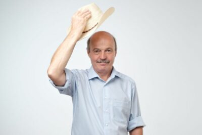 mature man waving with cowboy hat in studio. Welcoming his guests. Texas citizen concept.
