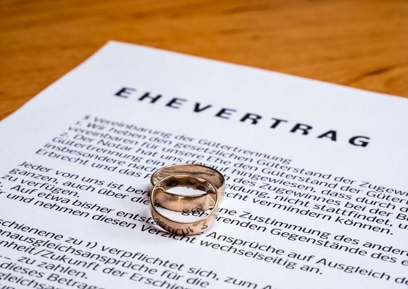 """Dokument mit der Aufschrift """"Ehevertrag"""" und Eheringe"""