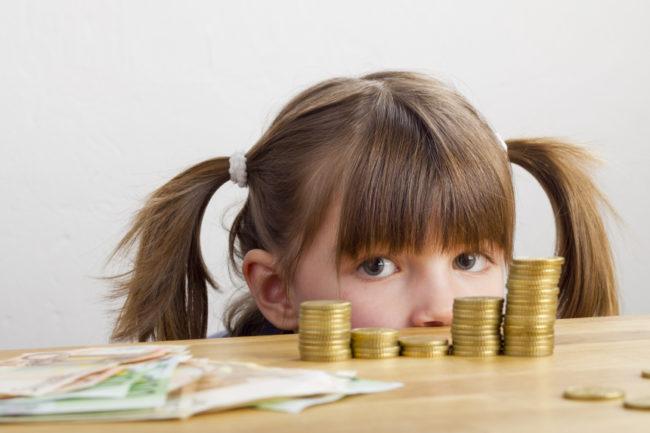 kleines Mädchen schaut auf einen Stapel Münzen und Geldscheine