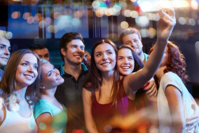 smiling friends with smartphone taking selfie in club