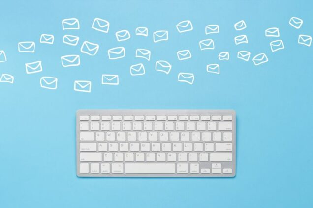 Keyboard on a blue background and flying envelopes. Concept global network, e-mail, correspondence, many e-mails. Flat lay, top view