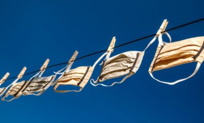Protective face masks hanging on the line and blue sky at background