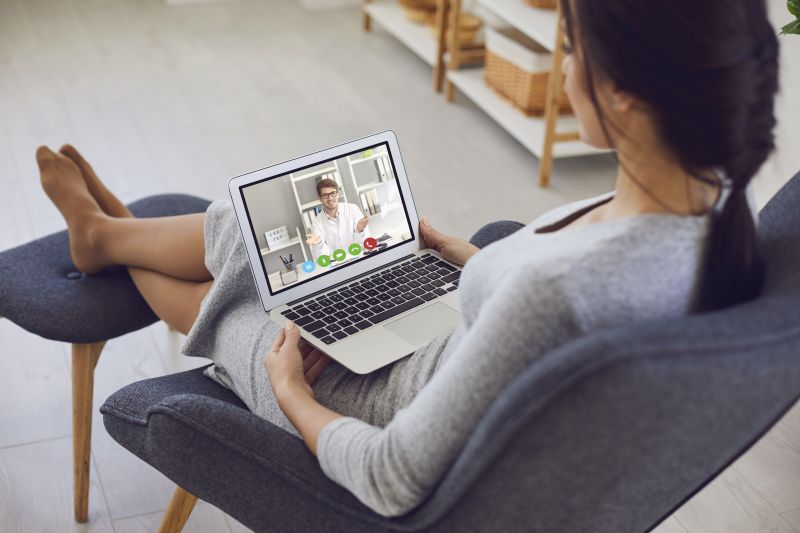 A sick young woman video chat with a male doctor sitting at home. Online medical consultation.