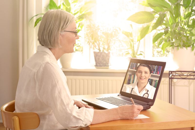 Senior woman in her sunny living room in front of a laptop making notes during a video call with her female doctor