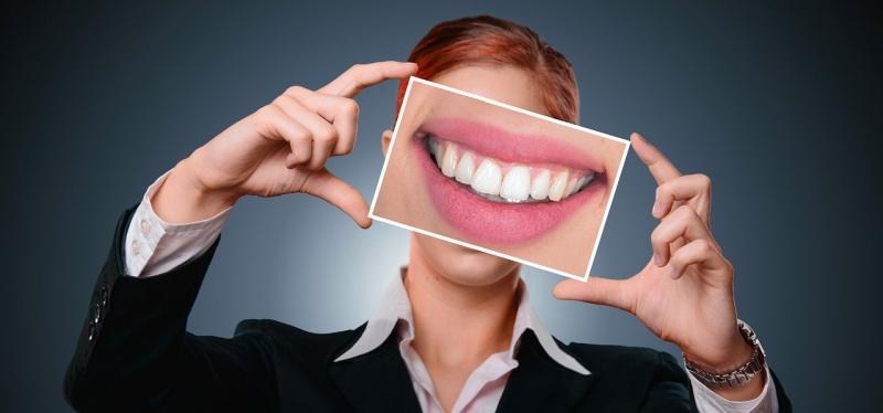 Frau hält Bild mit Zähnen hoch