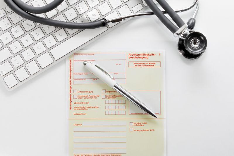 Arbeitsunfähgkeitsbescheinigung auf dem Schreibtisch einer Arztpraxis