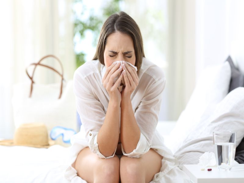 Ill woman coughing in an hotel room on summer vacations on the beach