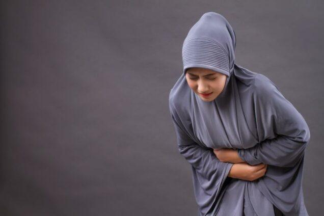 Verschleierte Frau mit Magenschmerzen