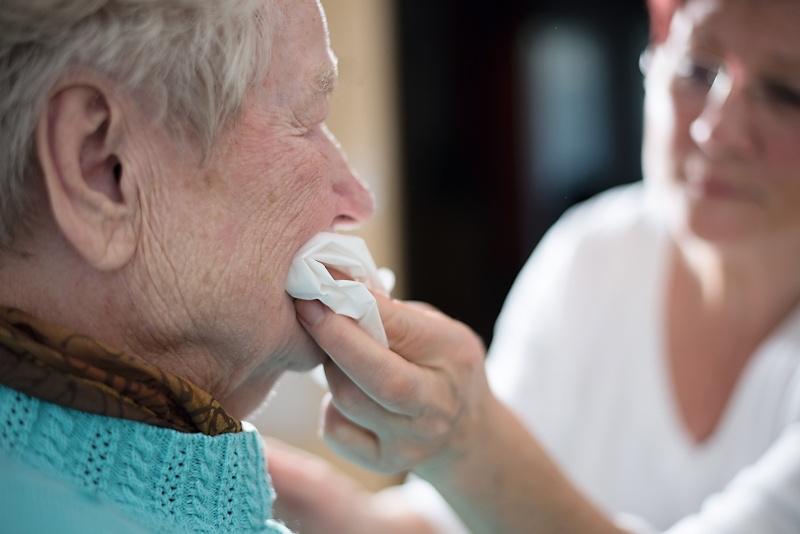 Krankenpflegerin wischt älteren Frau den Mund ab