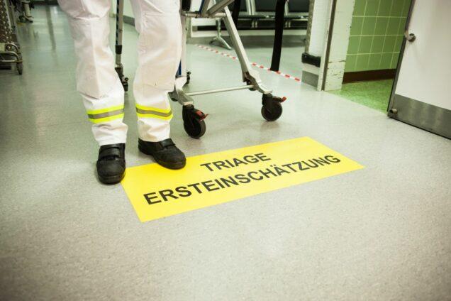 Triage Schild auf dem Boden einer Notaufnahme mit Sanitäter