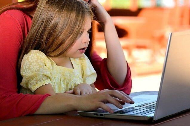 Frau sitzt mit Kind auf dem Schoß am Laptop