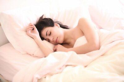 Frau liegt schlafend im Bett