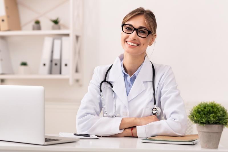 Lachende Ärztin am Schreibtisch