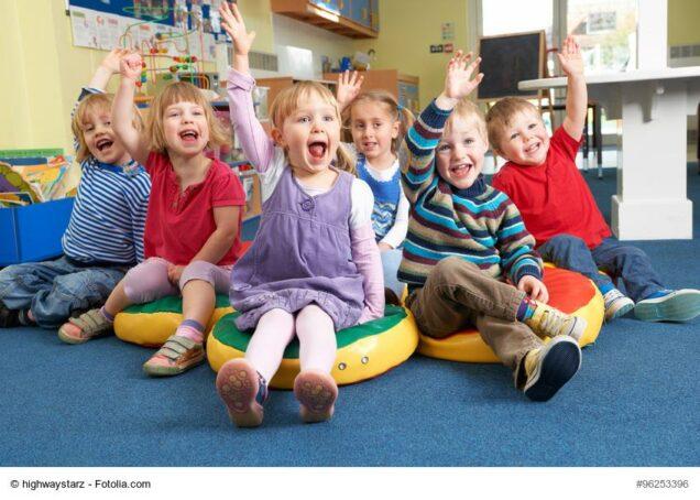 Kinder im Kindergarten strecken Arme nach oben