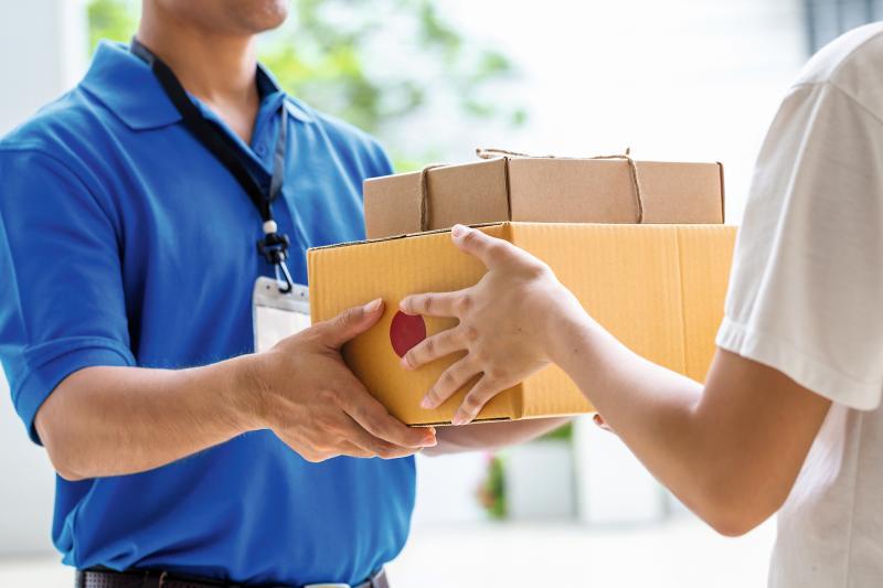 Paketbote gibt Paket an Arzthelferin