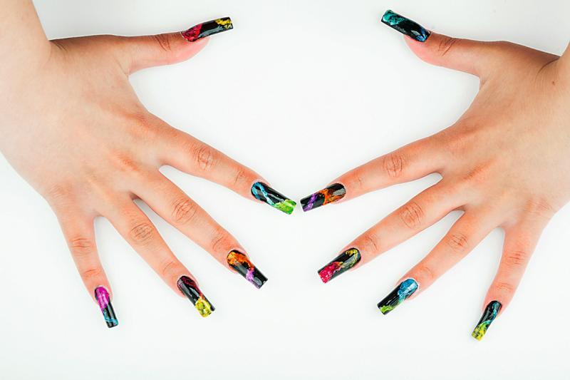 Frauenhände mit alngen, lackierten Fingernägeln