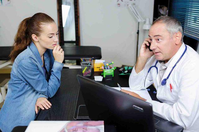 Junge Frau im Gespräch mit einem Arzt, der telefonisch Rücksprache hält