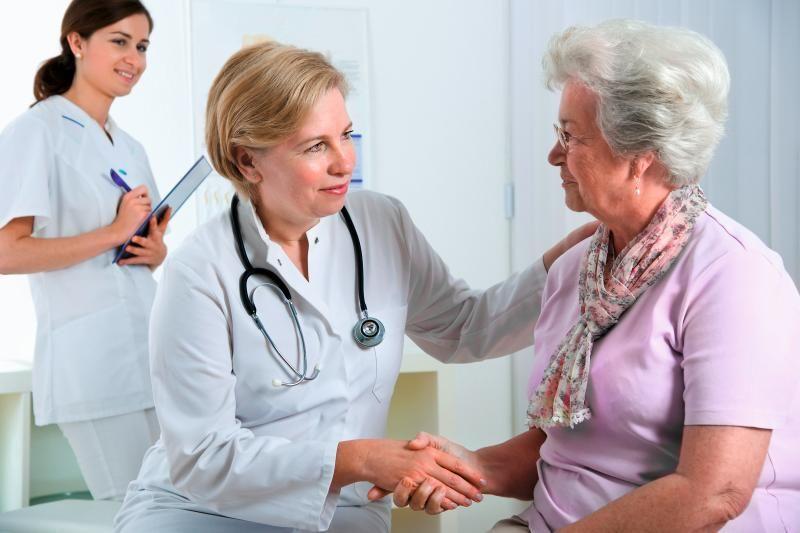 Ärztin gibt Patientin die Hand. Im Hintergrund lächelt eine MFA