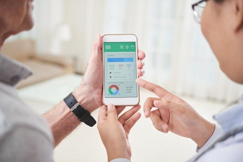 Arzt zeigt Patientin eine Gesundheitsapp au fdme Smartphone