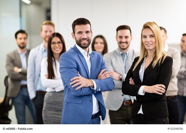 Mann und Frau, beide Manager, lächeln in die Kamera, im Hintergrund stehen Mitarbeiter
