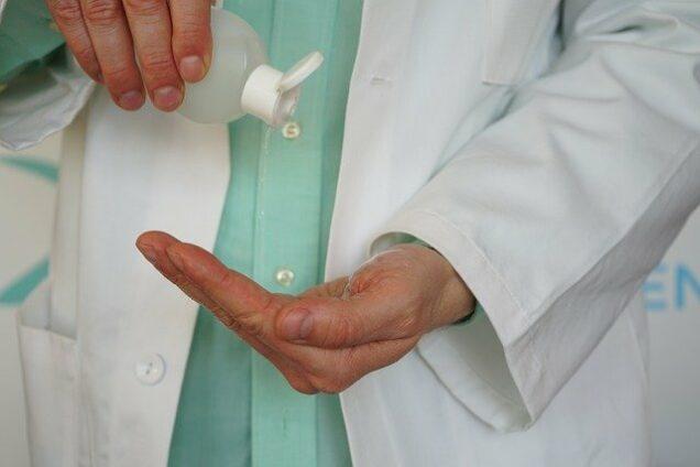 Arzt desinfiziert sich die Hände mit Desinfektionsmittel