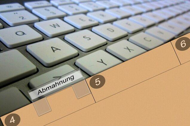 Mappe mit der Aufschrift Abmahnung auf einer Tastatur