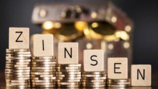 Würfel mit den Buchstaben des Wortes Zinsen auf abfallenden Stapeln mit Münzen