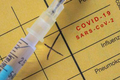 Impfpass mit einem Kreuz bei Covid-19-SARS-CoV-2 und einer Spritze mit Covid-19-Impfstoff