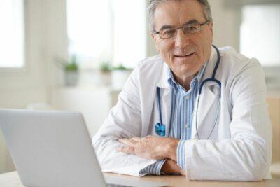 Älterer Arzt am Laptop