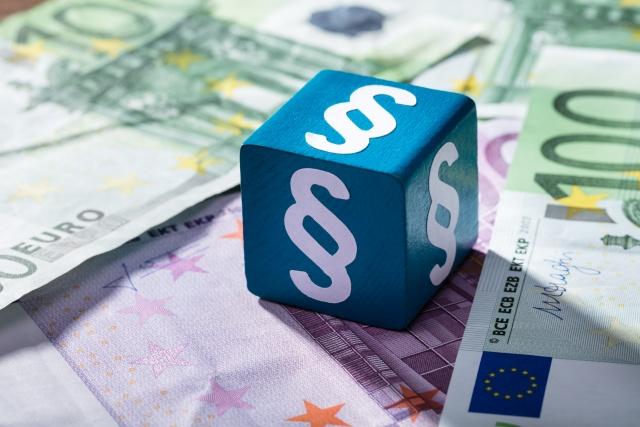 Würfel mit Paragrafen-Zeichen auf Geldscheinen