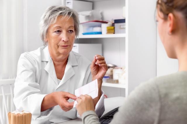 Arztin überreicht Rezept an Patientin