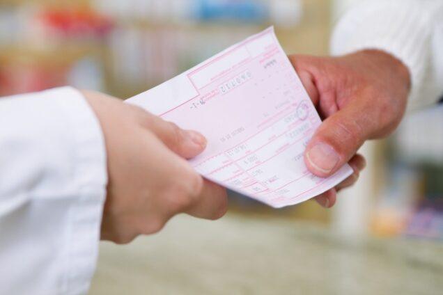 Arzthelferin gibt Arzt ein Rezept zur Unterschrift