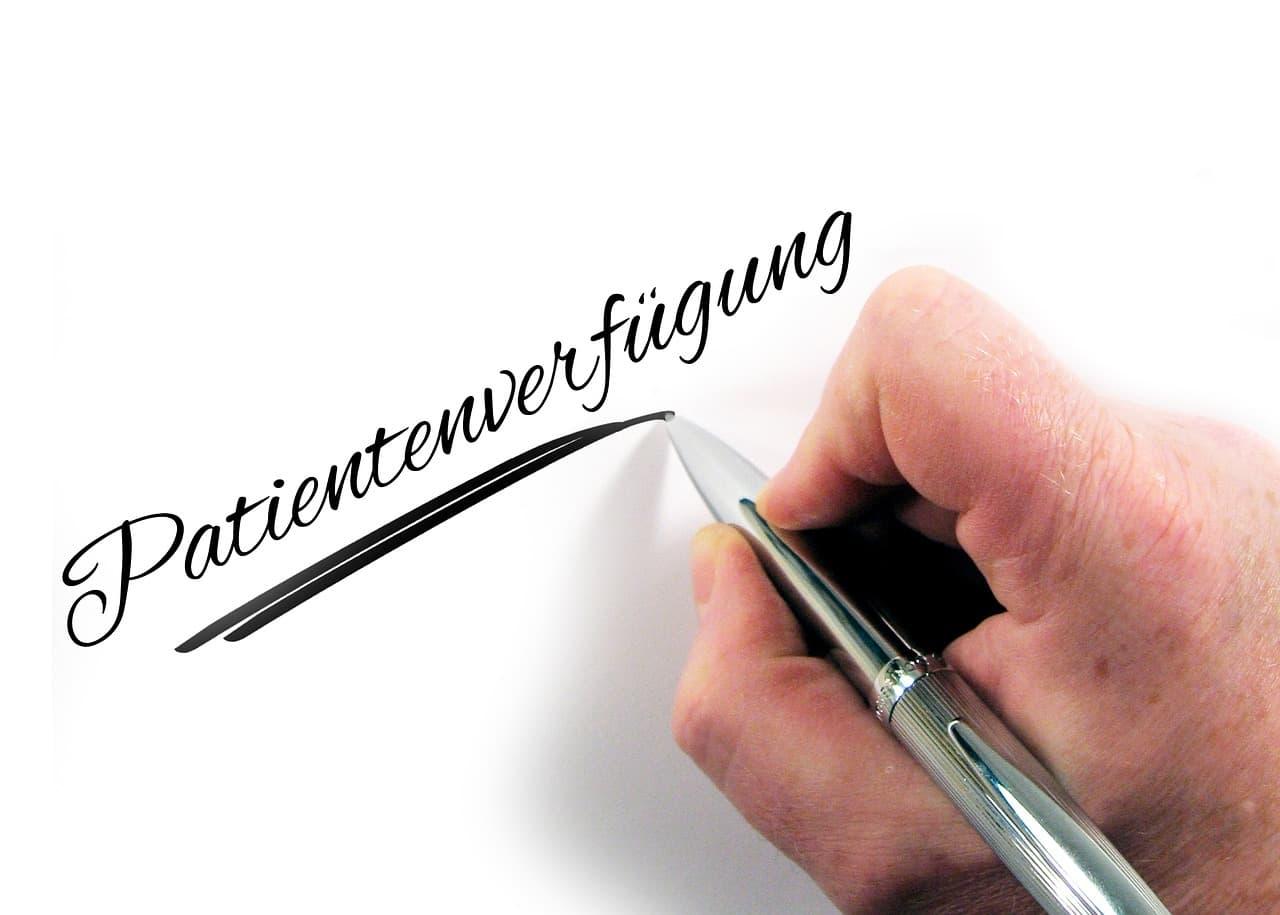 Person schreibt Patientenverfügung auf ein Blatt Papier