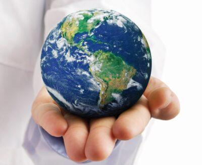 Hand eines Arztes hält eine Weltkugel