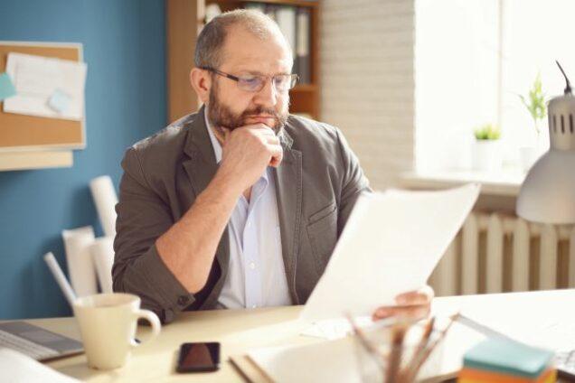 Mann am Schreibtisch schaut nachdenklich auf ein Formular