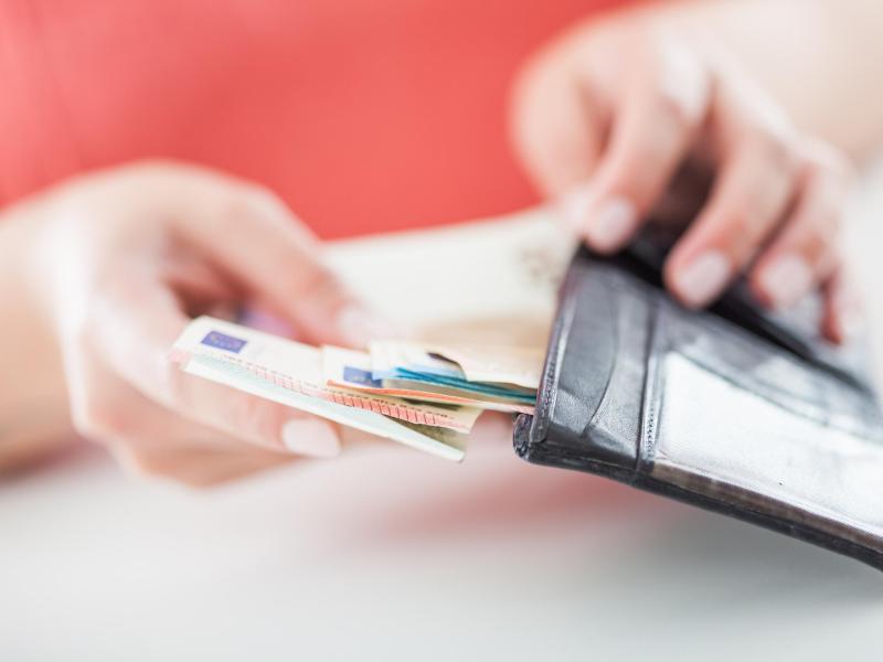 Frau steckt Scheine in Geldbörse