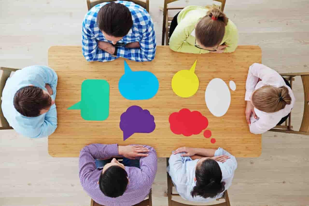 Menschen an einem Tisch mit Sprechblasen