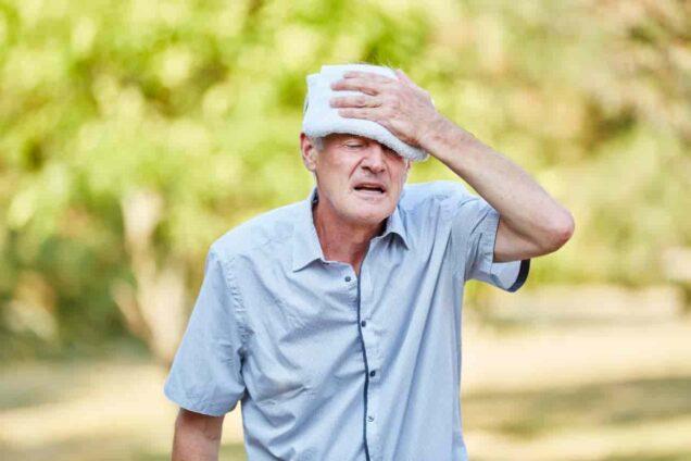 Älterer Mann legt sich gegen die Hitzebelastung einen Waschlappen auf die Stirn