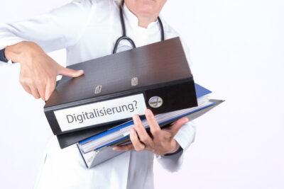 Arzt mit Aktenordner mit der Aufschrift Digitalisierung