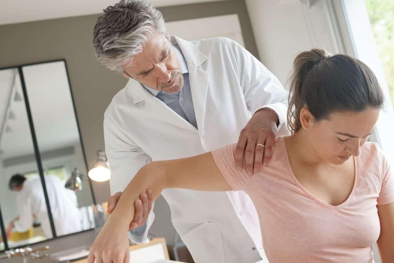 Patientin mit Schmerzen in der Schulter beim Arzt